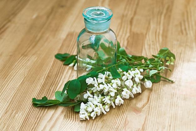 Wiązka białych kwiatów akacja blisko butelki medycyny