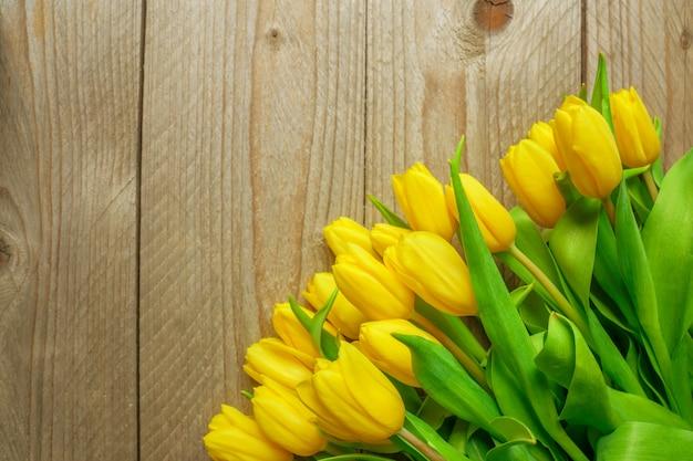 Wiązka bloomig żółci tulipany na drewnianym tle. miejsce na tekst, obraz bez tekstu