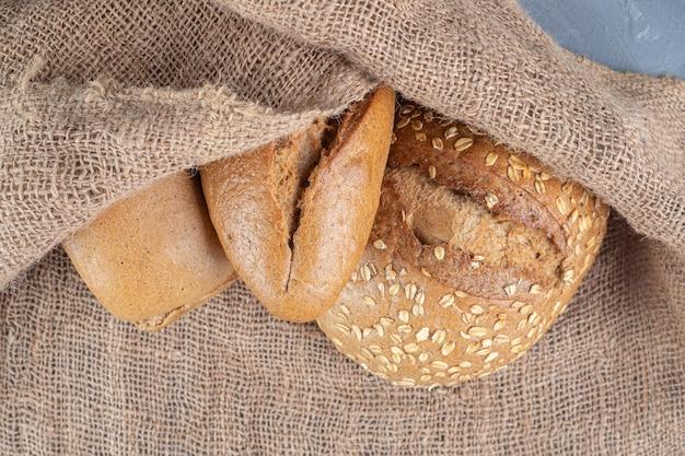 Wiązka bochenków chleba przykryta kawałkiem tkaniny na marmurowym stole.