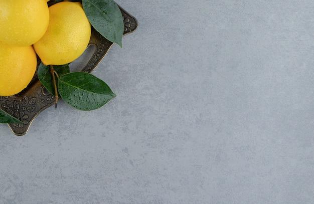 Wiązka cytryn i liści na ozdobnej tacy na marmurze