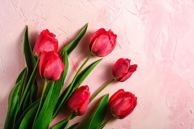 Wiązka czerwoni tulipanowi kwiaty na textured różowym tle, odgórnego widoku kopii przestrzeń