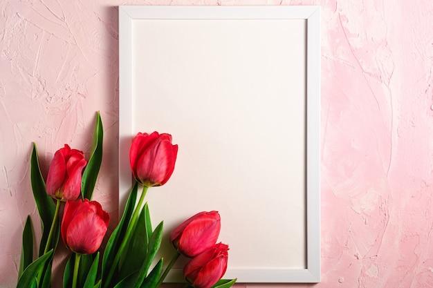 Wiązka czerwoni tulipanowi kwiaty z obrazek ramy szablonem na textured menchii ścianie, odgórnego widoku kopii przestrzeń