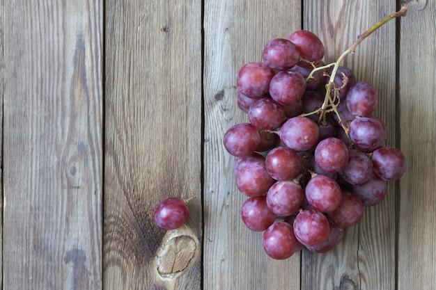 Wiązka czerwoni winogrona na drewnianym stole. skopiuj miejsce