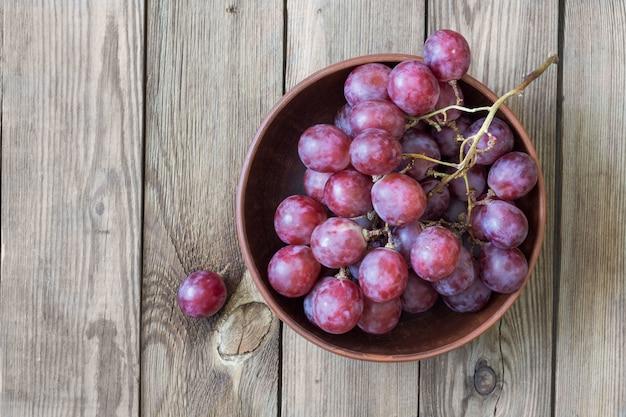 Wiązka czerwoni winogrona w pucharze na drewnianym stole. skopiuj miejsce styl rustykalny