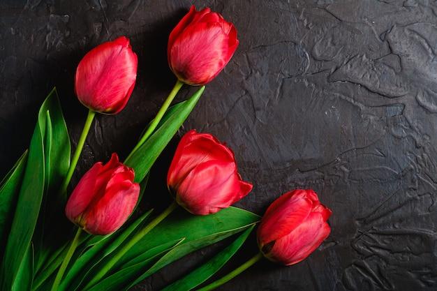 Wiązka czerwony tulipan kwitnie na textured czarnym tle, odgórnego widoku kopii przestrzeń