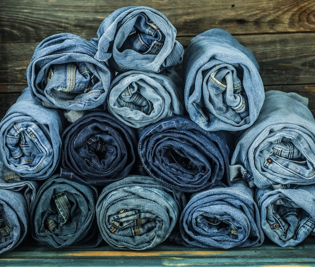 Wiązka dżinsów skręconych na drewnianej ścianie, modne ciuchy