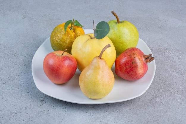 Wiązka granatu, gruszek, mandarynki, pigwy i jabłka na talerzu na marmurowym tle.