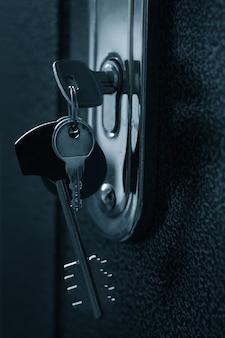 Wiązka kluczy w dziurce od klucza drzwi