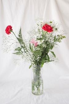 Wiązka kwiaty z zielonymi liśćmi w wazie