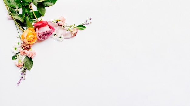 Wiązka mali kwiaty z różami układać nad białym tłem