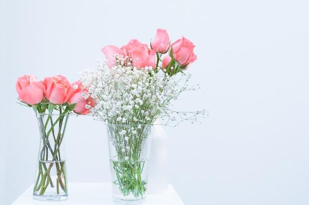 Wiązka menchii róży eustoma kwitnie w szklanej wazie na białym tle
