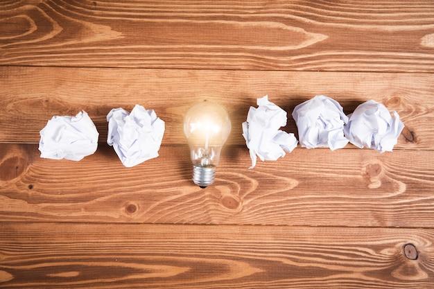 Wiązka papieru i lampa na drewnianej powierzchni