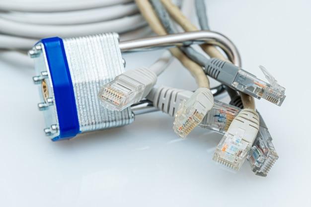 Wiązka przewodów sieciowych zablokowana metalową kłódką na białym tle