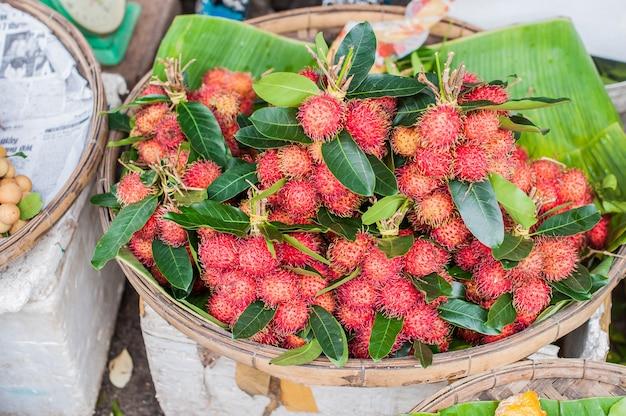 Wiązka rambutan w wiklinowym koszu na wietnamskim rynku