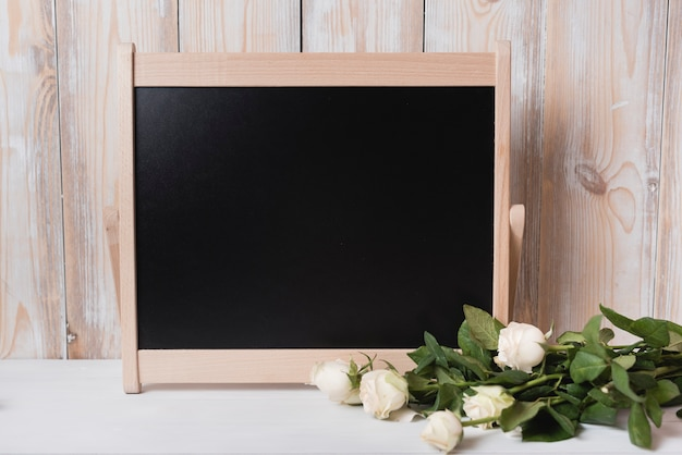 Wiązka róże z drewnianym małym blackboard na białym biurku