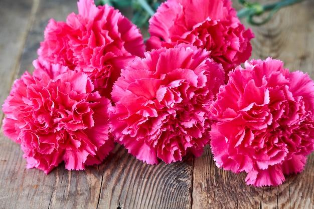 Wiązka różowi goździki na stary drewnianym