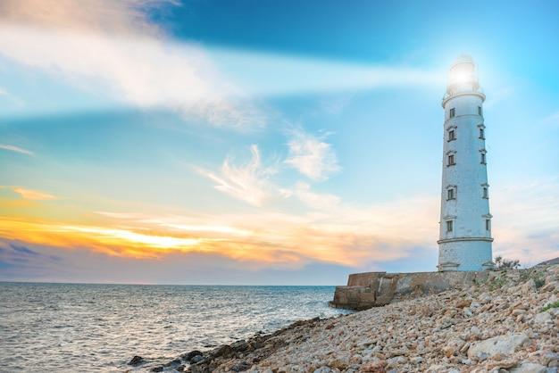 Wiązka szperacza latarni morskiej w nocy. pejzaż morski o zachodzie słońca