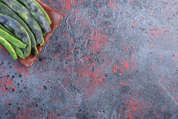 Wiązka ziaren strączkowych na talerzu na czarnym stole.