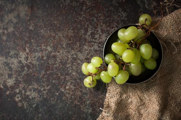 Wiązka zieleni gronowi winogrona na ciemnym tle.