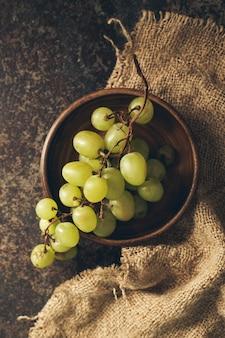 Wiązka zieleni winogrona na ciemnym tle.