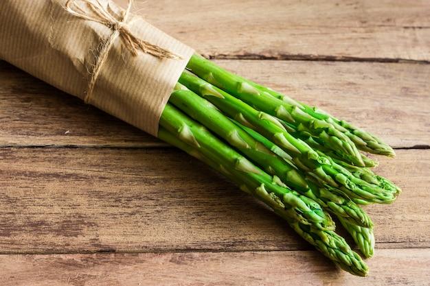 Wiązka zielony świeży asparagus wiążący z dratwy lying on the beach na starzejącym się deski drewna stole
