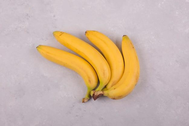 Wiązka żółtych bananów na białym tle na betonie w centrum