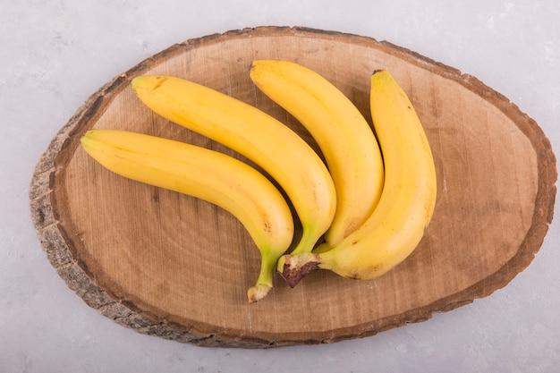 Wiązka żółtych bananów na białym tle na tle betonu na kawałku drewna
