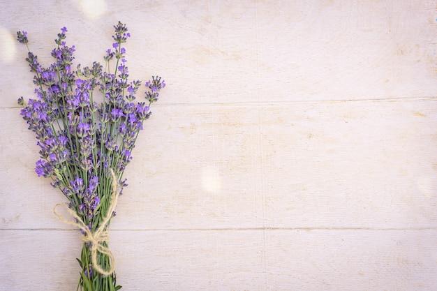 Wiązka związanych kwiatów lawendy na białym drewnianym tle