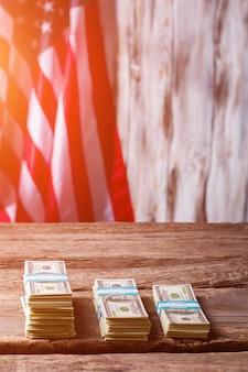 Wiązki amerykańskiej flagi i dolara. wiązki gotówki obok flagi. kapitał rośnie. zarabiaj i pomnażaj.