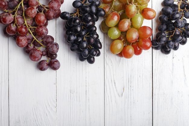 Wiązki dojrzali winogrona na drewnianym stole. widok z góry.