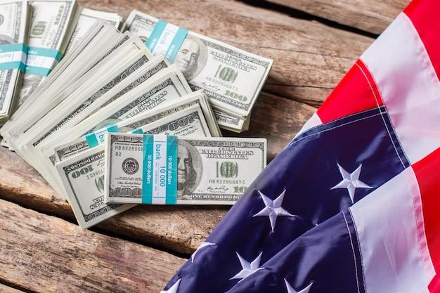 Wiązki flagi usa i dolara. flaga leżąca w pobliżu wiązek gotówki. owoce dyplomacji. wolność i bogactwo.