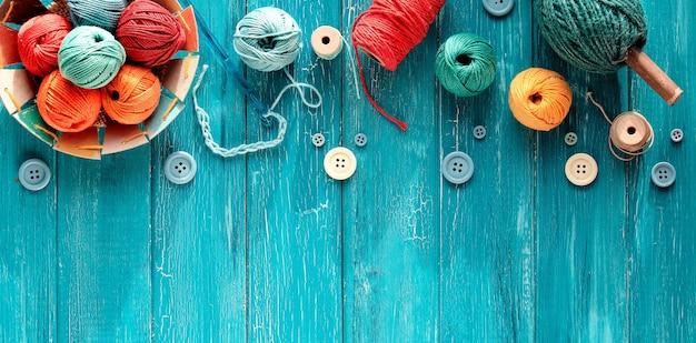 Wiązki wełny, kulki z przędzy, guziki i sznurek. zatrzask i igły dziewiarskie na postarzanym turkusowym drewnie