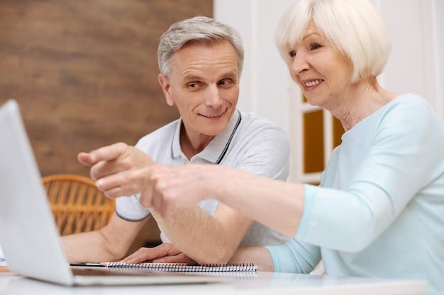 Wibrująca, aktywna rodzina seniorów pracująca nad nowym pomysłem podczas przeglądania jakiegoś dokumentu za pomocą laptopa
