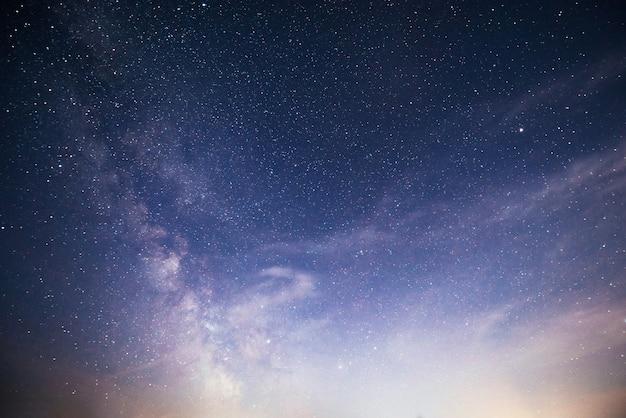 Wibrujące nocne niebo z gwiazdami, mgławicą i galaktyką.