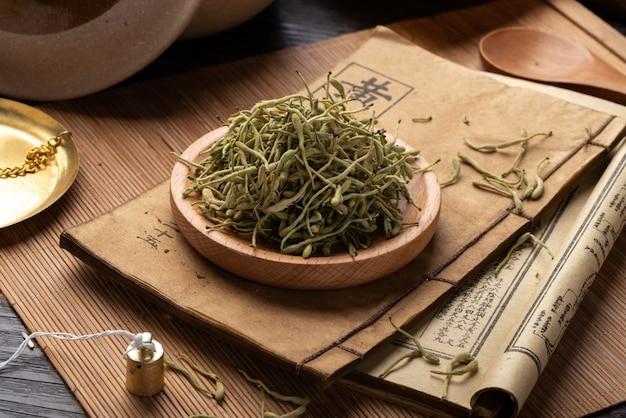 Wiciokrzew książki starożytnej medycyny chińskiej i zioła na stole