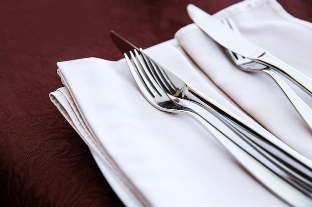 Widelec i nóż z bliska na białej serwetce. szczegóły restauracji?