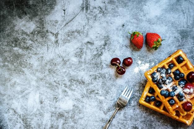 Widelec na rustykalnym stole gotowy na deser, gofr ze zdrowymi czerwonymi owocami.