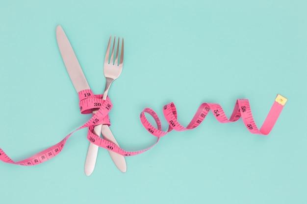 Widelec, nóż i taśma pomiarowa. pojęcie diety.