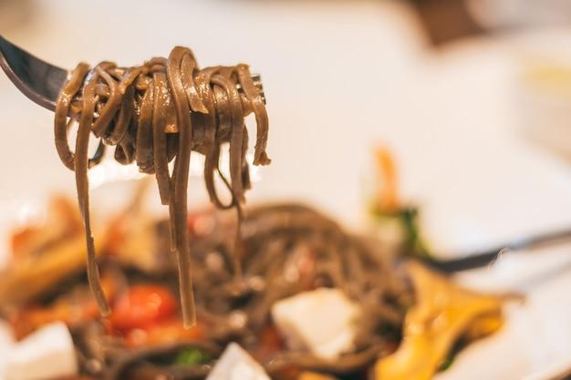 Widelec z makaronem gryczanym, na tle zamazanego talerza z wegańskim daniem