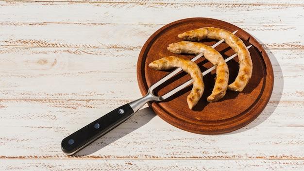 Widelec z pieczonymi kiełbaskami na talerzu