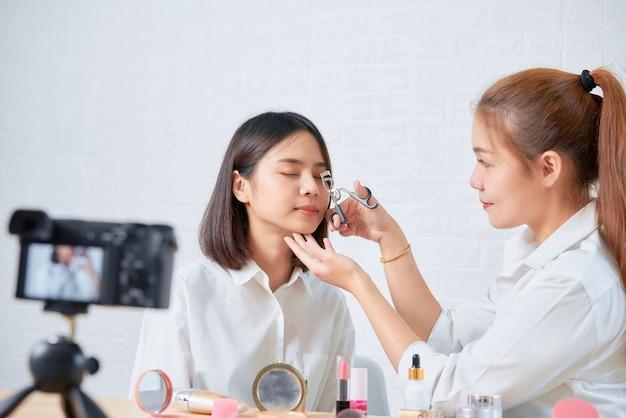 Wideo online dwóch młodych azjatek, vloggerów kosmetycznych, pokazuje makijaż na produktach kosmetycznych i wideo na żywo z cyfrowego aparatu fotograficznego.