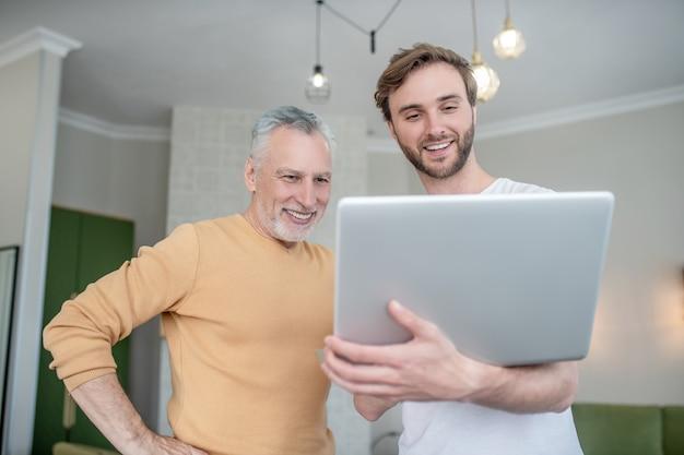 Wideo rozmowa. dwóch mężczyzn odbywa wideorozmowę i wygląda na podekscytowanych