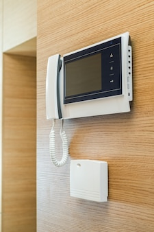 Wideodomofon z ekranem na ścianie z drewna