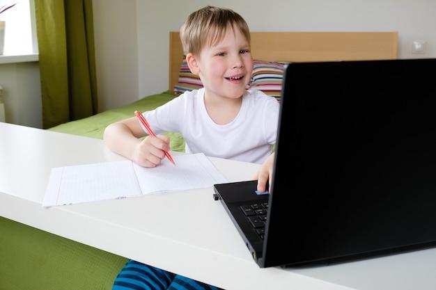 Wideokonferencja chłopca z korepetytorem na laptopie w domu. koncepcja kształcenia na odległość. zostań w domu