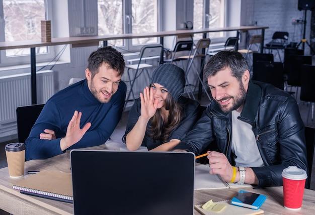 Wideokonferencja młodego inteligentnego zespołu grupa nowoczesnych ludzi wita się lub żegna na wideo