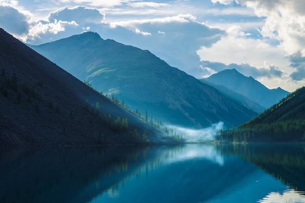 Widmowy górski jezioro w średniogórzach przy wczesnym porankiem. piękne mgliste sylwetki gór i chmur odbite w czystej powierzchni wody. dym z ognisk. niesamowity krajobraz majestatycznej przyrody.