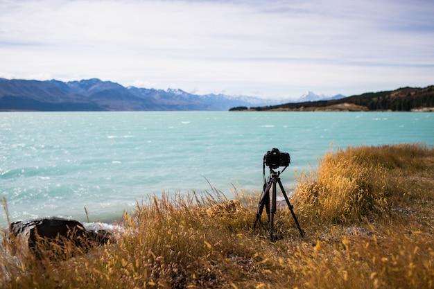 Widok aparatu fotograficznego na statywie nad pięknym jeziorem i wzgórzami na horyzoncie w słoneczny dzień