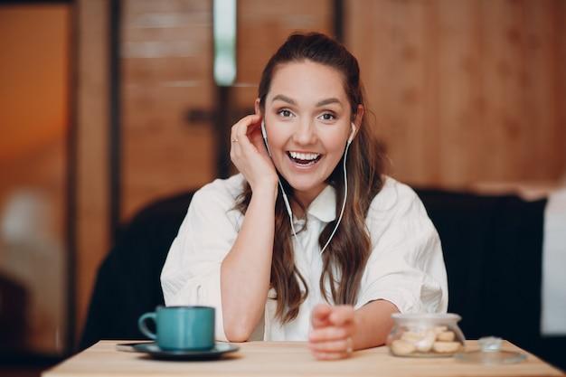 Widok aplikacji na ekranie uśmiechniętej młodej kobiety siedzącej przy stole z laptopem i rozmawiającej podczas rozmowy wideo z przyjacielem lub współpracownikiem, szczęśliwa dziewczyna z filiżanką herbaty lub kawy rozmawiająca online na kamerze internetowej w pomieszczeniu konferencyjnym