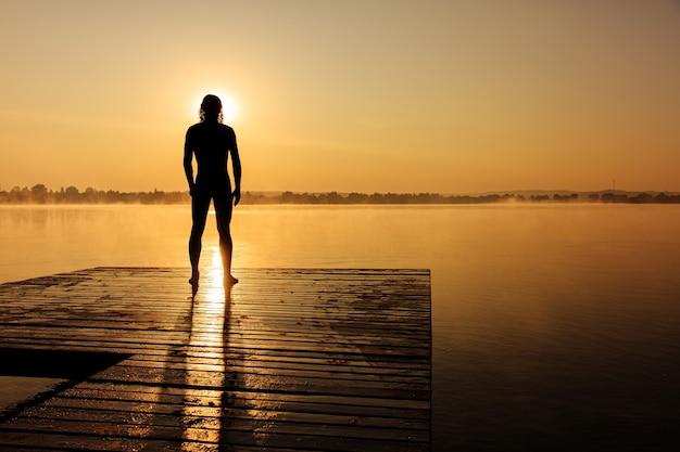 Widok atletycznego mężczyzny stojącego na drewnianym molo z tyłu i przygotowań do kąpieli w jeziorze podczas letniego wschodu słońca.
