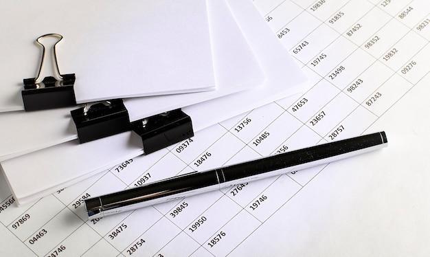 Widok biznesowy - wykres, długopis i dokumenty na białym stole, koncepcja
